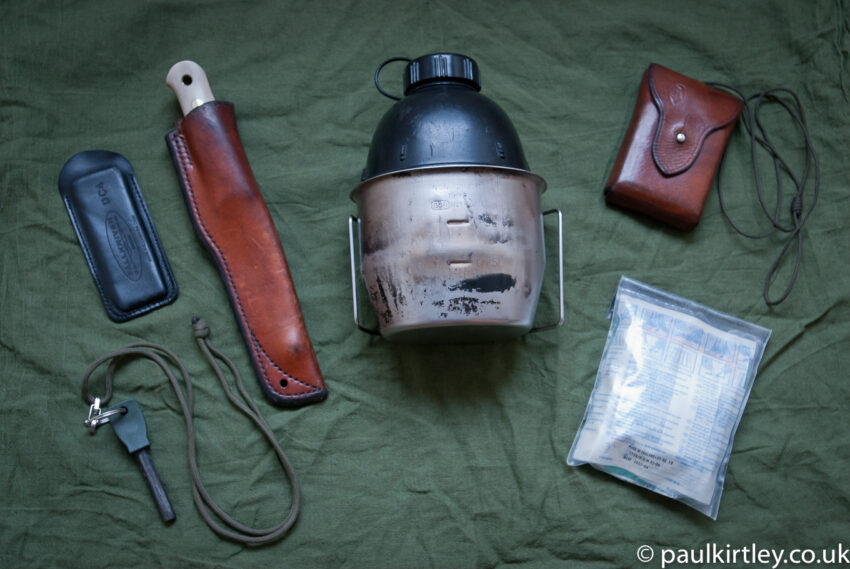 Paul Kirtley's essential wilderenss equipment - firesteel, whetstone, belt knife, metal mug, bottle, compass, first aid kit