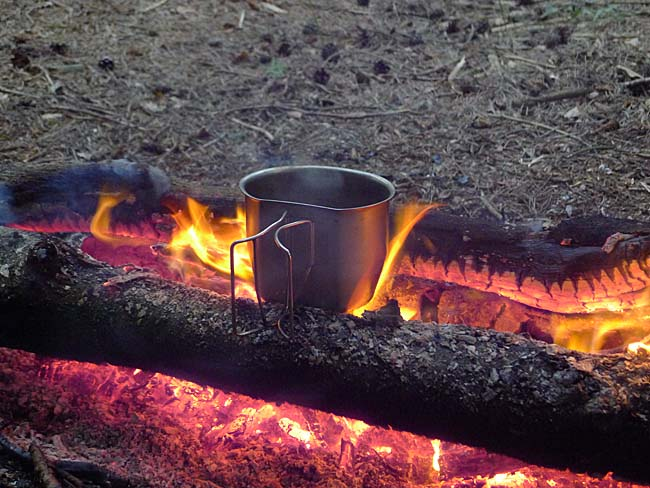 Boiling water in a metal mug on the fire