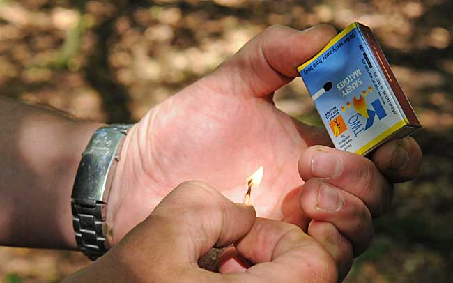 Lighting a camp fire - Cup your hands around the match