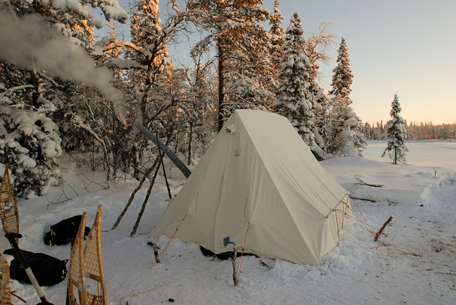 Canvas wall tent in snow with snowshoes and snow shovel
