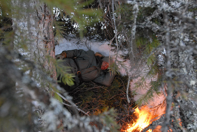 Man lying in front of fire in an improvised shelter