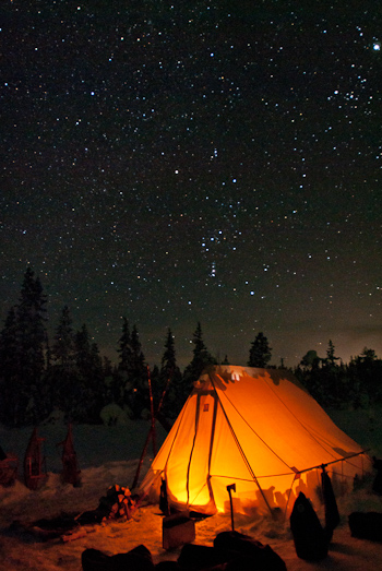 Orion constellation over illuminated canvas tent