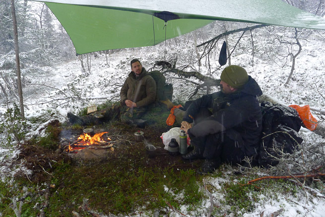 Two men sitting under a tarp with a fire surrounded by snow
