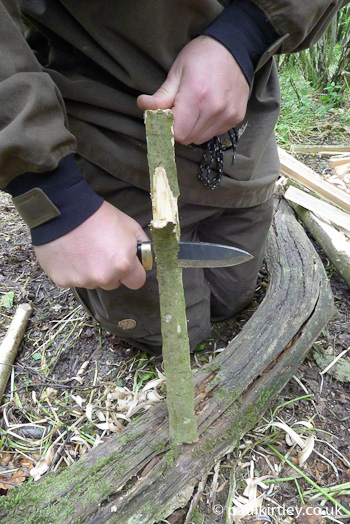 Shaving off the damp outer layers, including bark using a knife