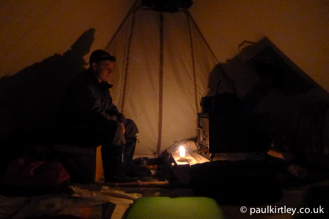 Man watching stove in a tent