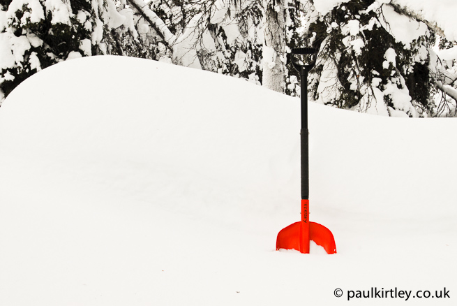 Red coloured Black Diamond snow shovel in white snow