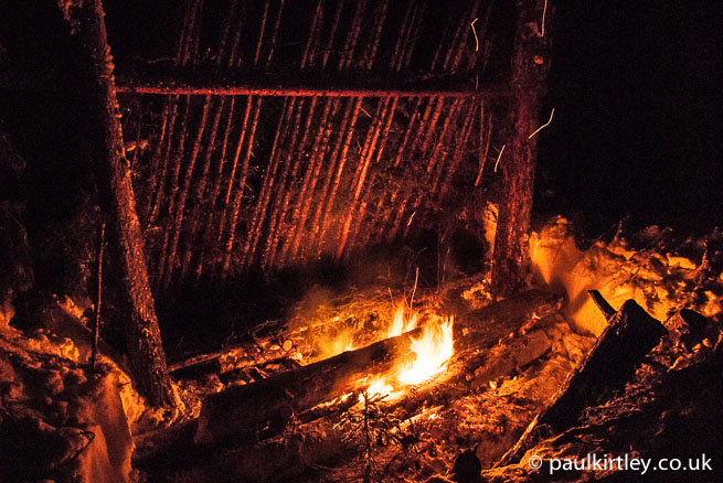 Long log fire in front of shelter