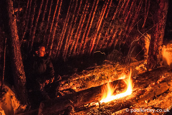 Man sitting with long log or neuing fire