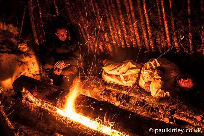 Two winter bushcraft guys in a classic lean-to shelter with textbook long-log fire