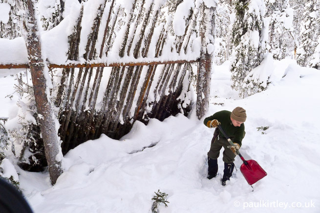Man digging snow in front of a lean-to shelter.