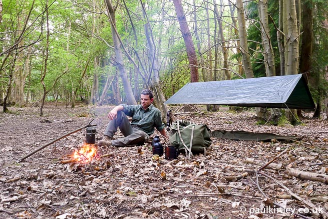 Bushcraft enthusiast with camp set up in the woods