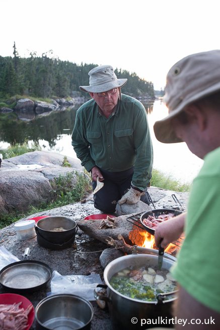 People cooking at campfire
