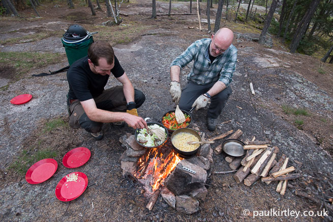 Two men cooking on a campfire