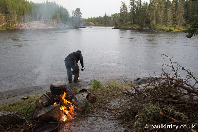 Fire and man collecting water from river in the rain