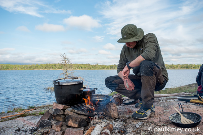 Man next to cooking pots on a fire