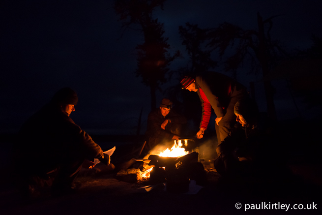 People illuminated by firelight