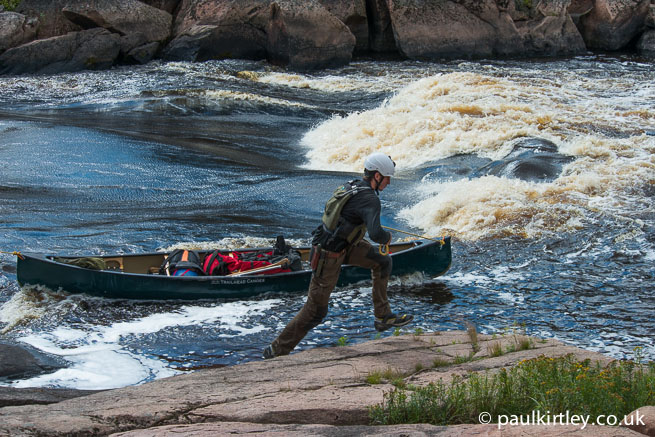 Man moving quickly while lining a canoe in powerful flow
