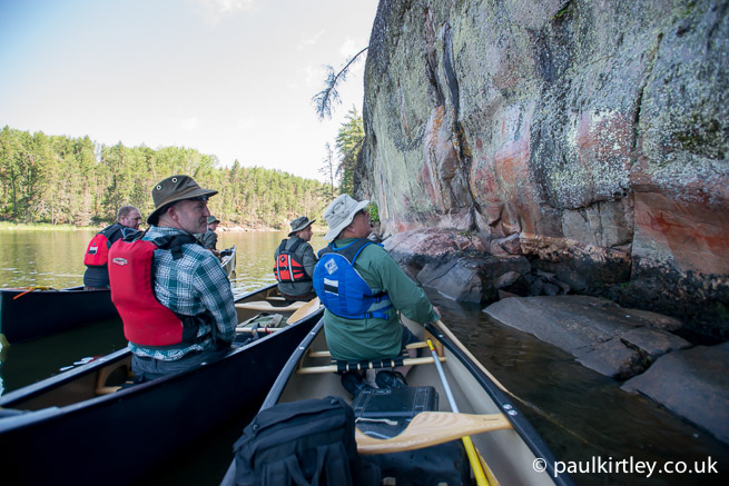 Group sitting in canoes looking at the Artery Lake pictographs