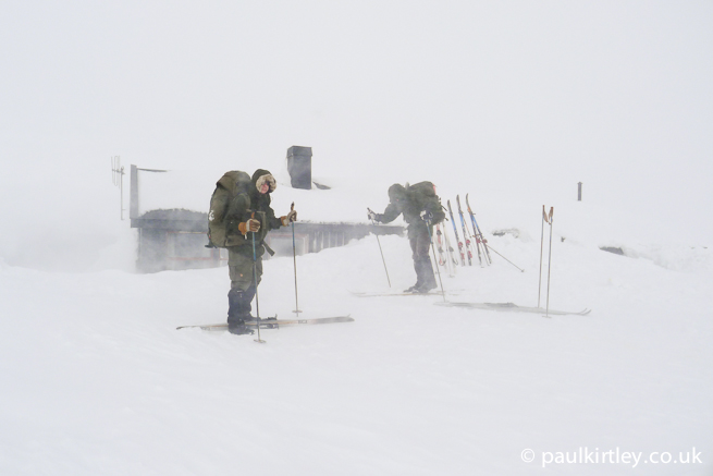 Two men in front of a hut in near blizzard conditions