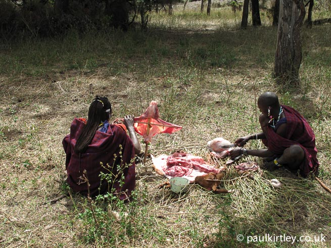 Masai men preparing goat offal