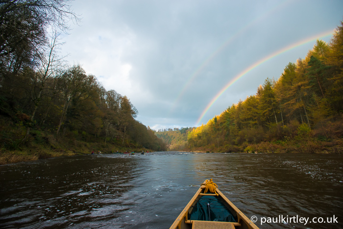 Double rainbow with river stretching into the distance and golden larches on the banks