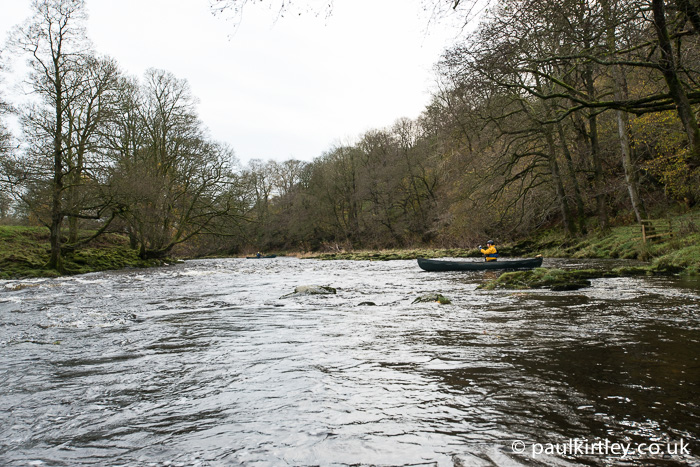 Two canoeists at different stages down a river