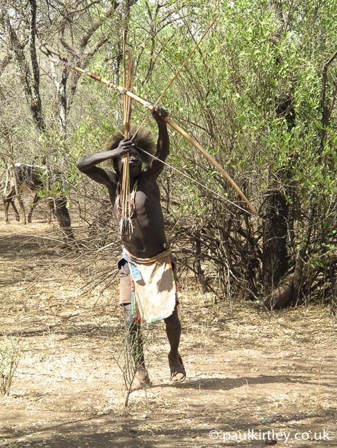 Hadza man hunting with bow