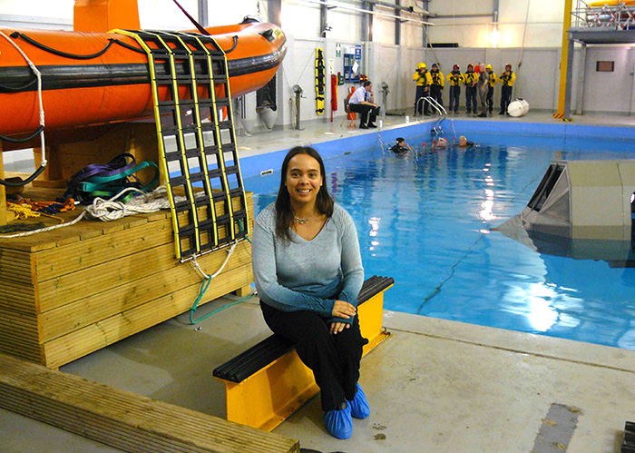 Dr Sarita Robinson sitting in front of training pool for helicopter underwater evacuation training and life rafts