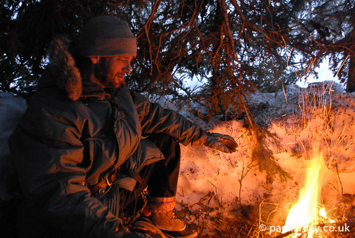 Man inside a tree shelter with a fire
