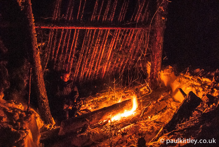 Lean to shelter illuminated by firelight of long log fire