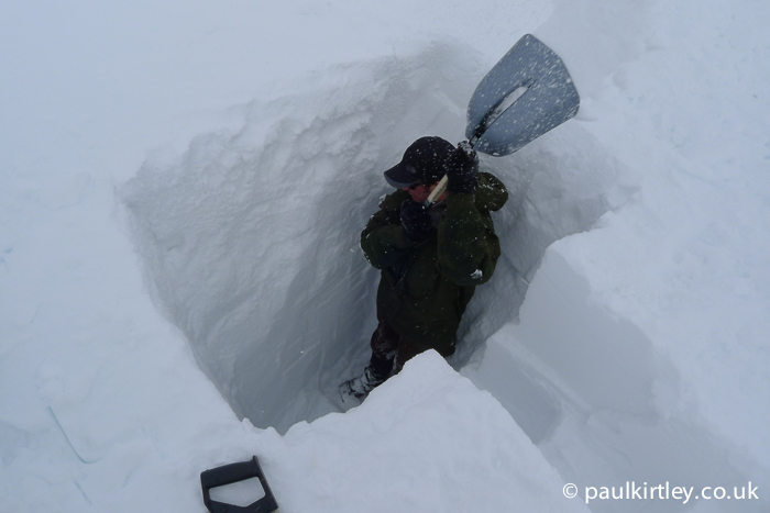 Man in a the two meter deep trench in the snow shovelling