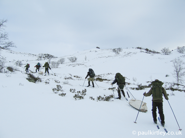Skiers struggling uphill with laden pulks