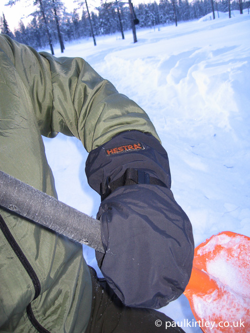 Hestra shell mitts on hand grasping orange Black Diamond snow shovel