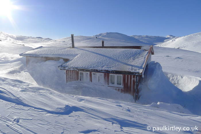 A hut in the snow with lots of spindrift