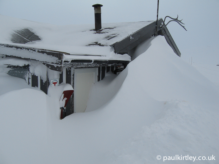 Hut with large snow drifts in front of it blocking the doorway