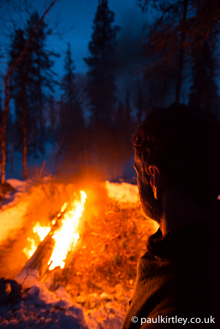 Man overlooking a burning long log fire