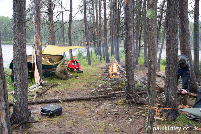 Canoes as windbreak, tarp and fire used in combination
