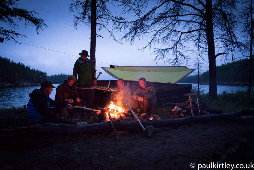 Five men sitting near fire in wilderness, waiting for the weather to change
