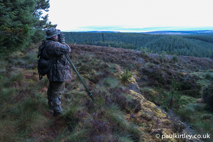 Man in drab clothing looking out over wild highland landscape using binoculars