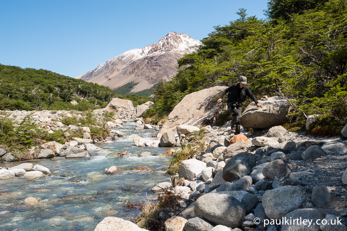 View of Alpine style river with blue glacial melt and woman walking along trail at side