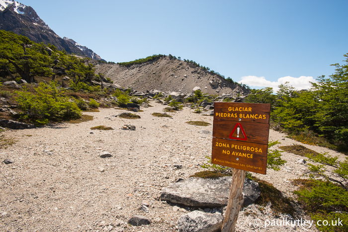 "Sign ahead of the Piedras Blancas Glacier stating ""Dangerous Area. Don't Proceed"""
