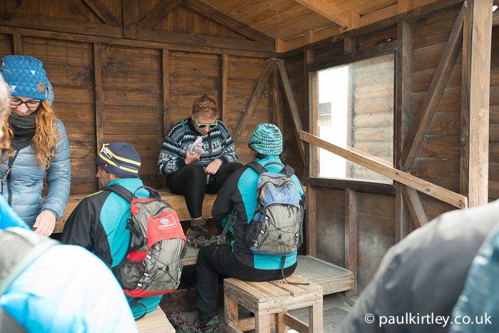 People sitting in a hut fitting crampons