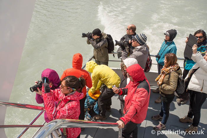 people standing on the rear deck of a boat taking photographs