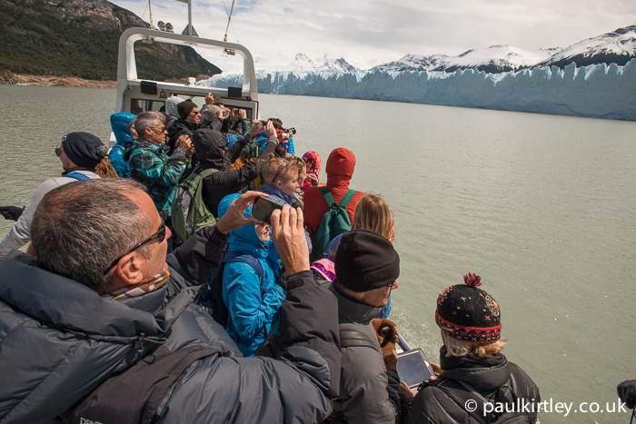Many people on deck of a boat taking photographs of a glacier, causing the boat to lean towards the glacier