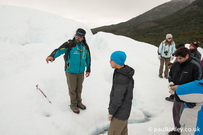 Guide explaining features of glacier to a group on Perito Moreno