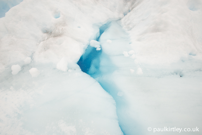 A water filled fissure in the ice of the glacier