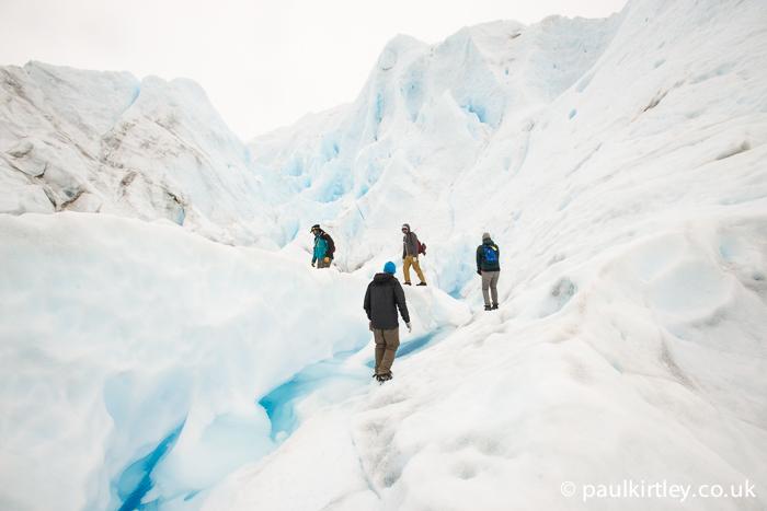 four people walking amongst serac on Perito Moreno glacier