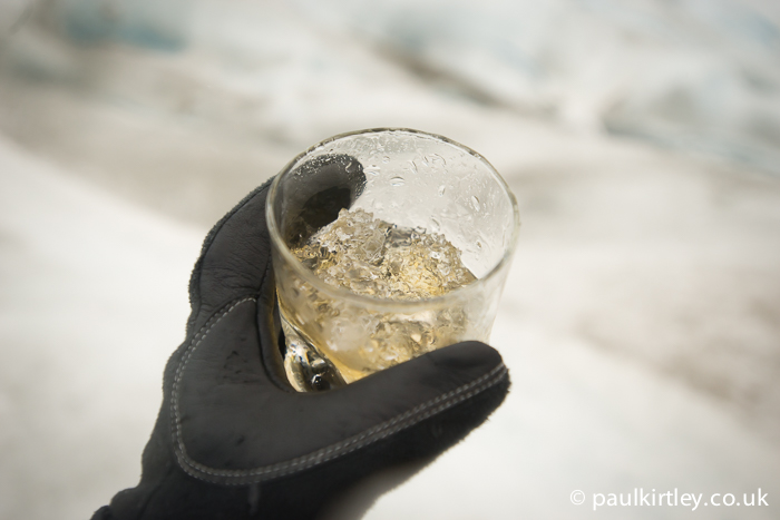 Glass with whisky and glacial ice with out of focus glacier in the background