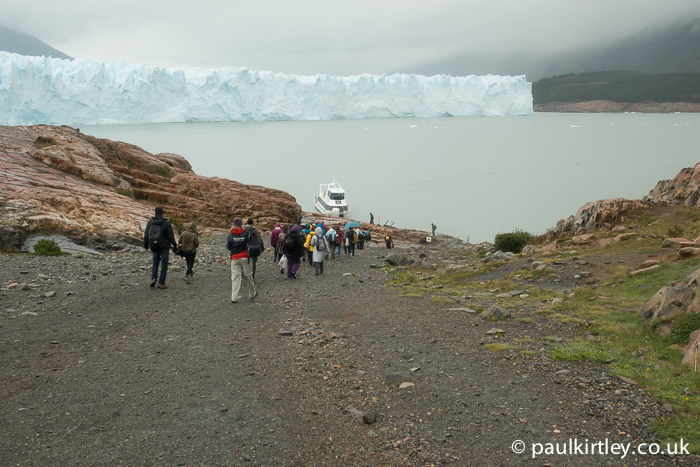 Tourists walking down a gravel track on a hill to the edge of a lake near a glacier