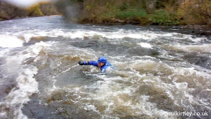 Man swimming in river rapids